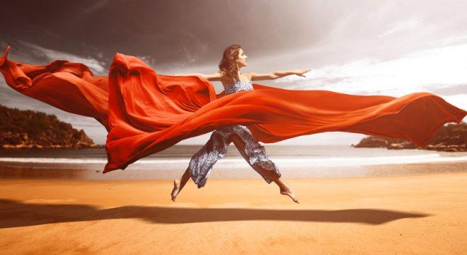 Frau springt am Strand zwischen fließenden Stoffen